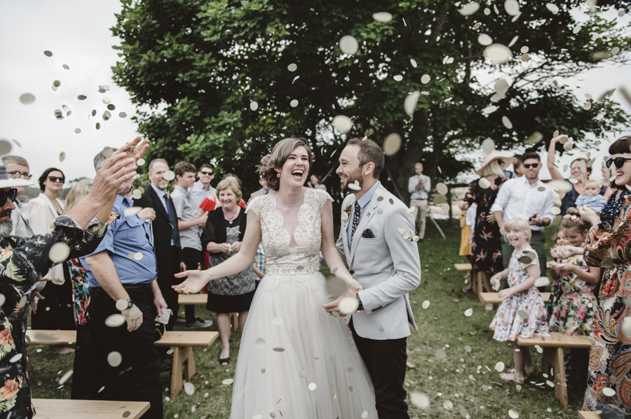 anthea-lyndon-exit-aisle-ceremony-outdoor-confetti-gold-bench-seats-lauren-campbell